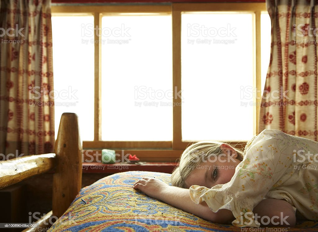 Girl (10-11) lying on bed royalty-free stock photo