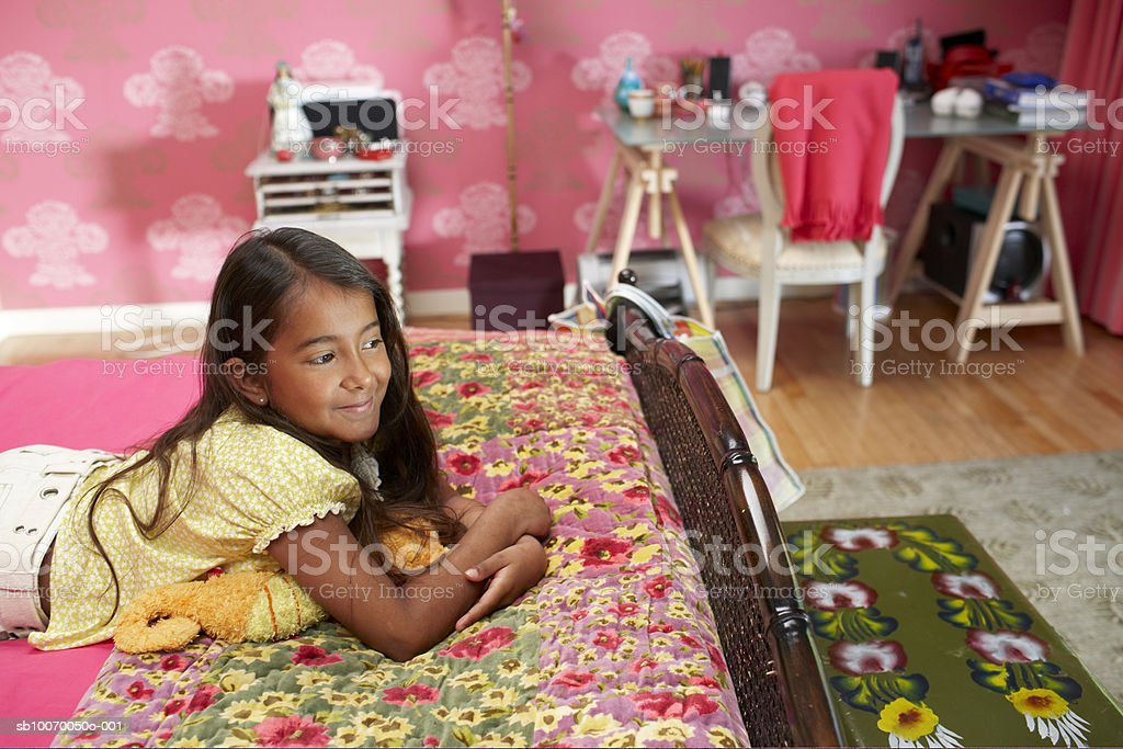Girl (frecuencia de 6-11) lying on bed, sonriendo, vista lateral foto de stock libre de derechos