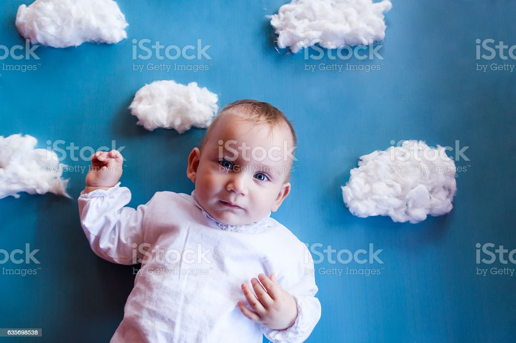 Girl lying on blanket with white clouds royalty-free stock photo