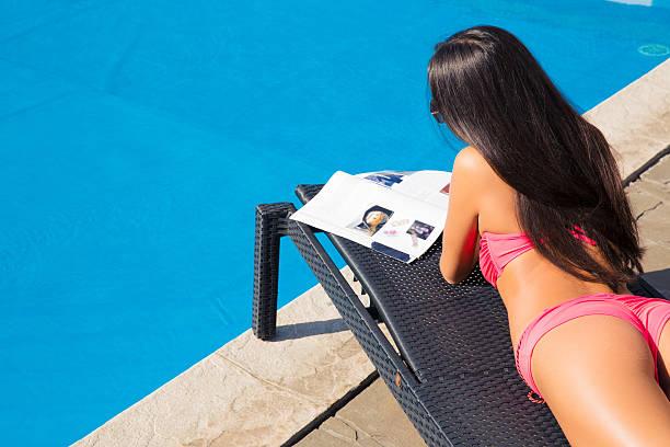 girl lying on deckchair and reading magazine - newspaper beach stockfoto's en -beelden
