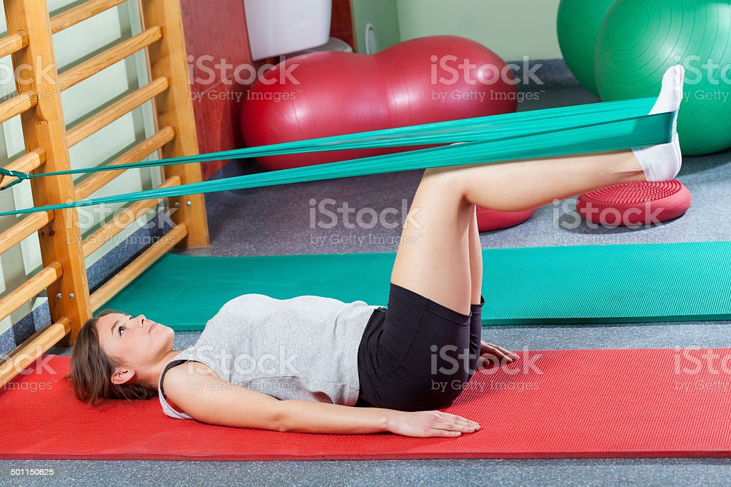 Girl lying on exercise mat and stretching legs stock photo