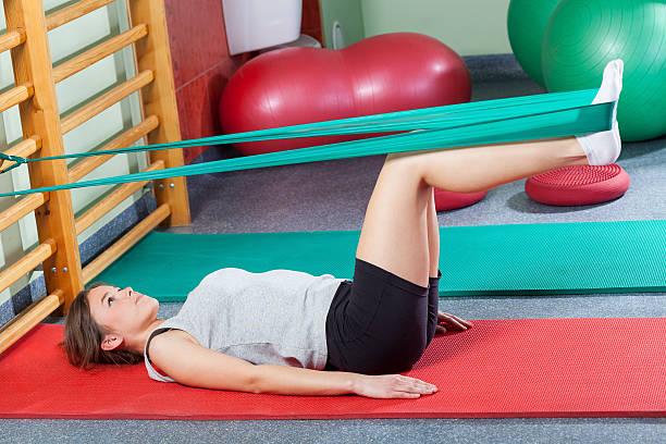 Girl lying on ejercicio, una estera de estiramiento y las piernas - foto de stock