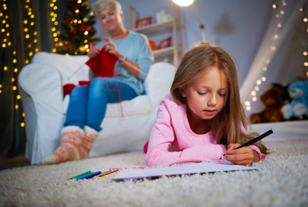 mädchen liegend auf vorderseite und zeichnung - ausmalbilder weihnachtsmann stock-fotos und bilder