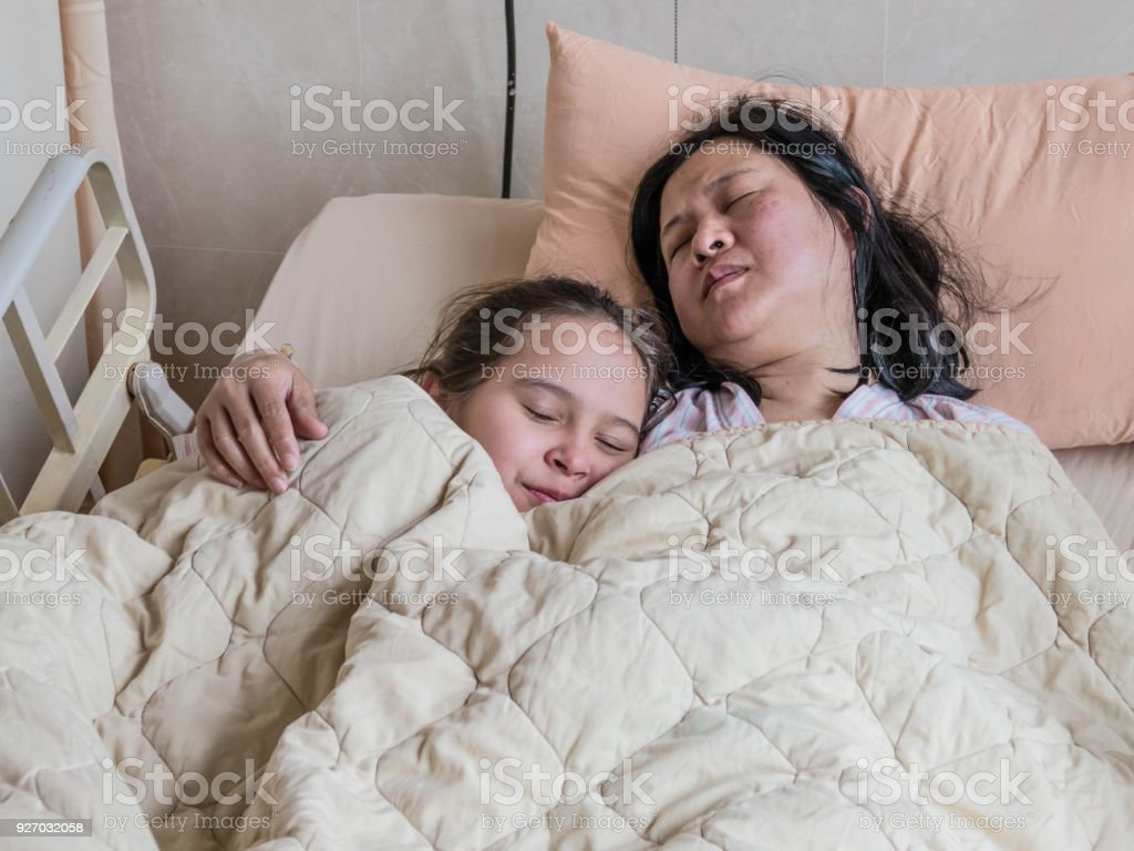 Girl lying on hopital bed next to sick mother stock photo