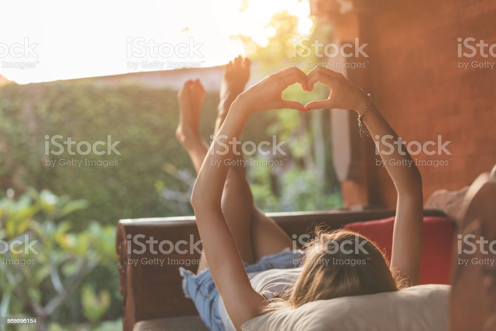 Girl lying on the garden sofa and holding a heart-shape. stock photo
