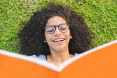 istock Girl lying on the grass and reading a book 1013103080