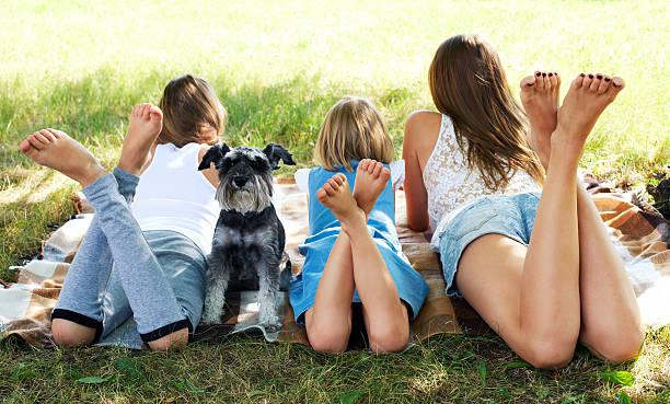 Mädchen auf dem Rasen liegen und ein Hund – Foto