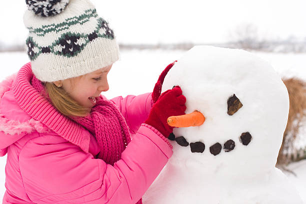 Girl make snowman stock photo