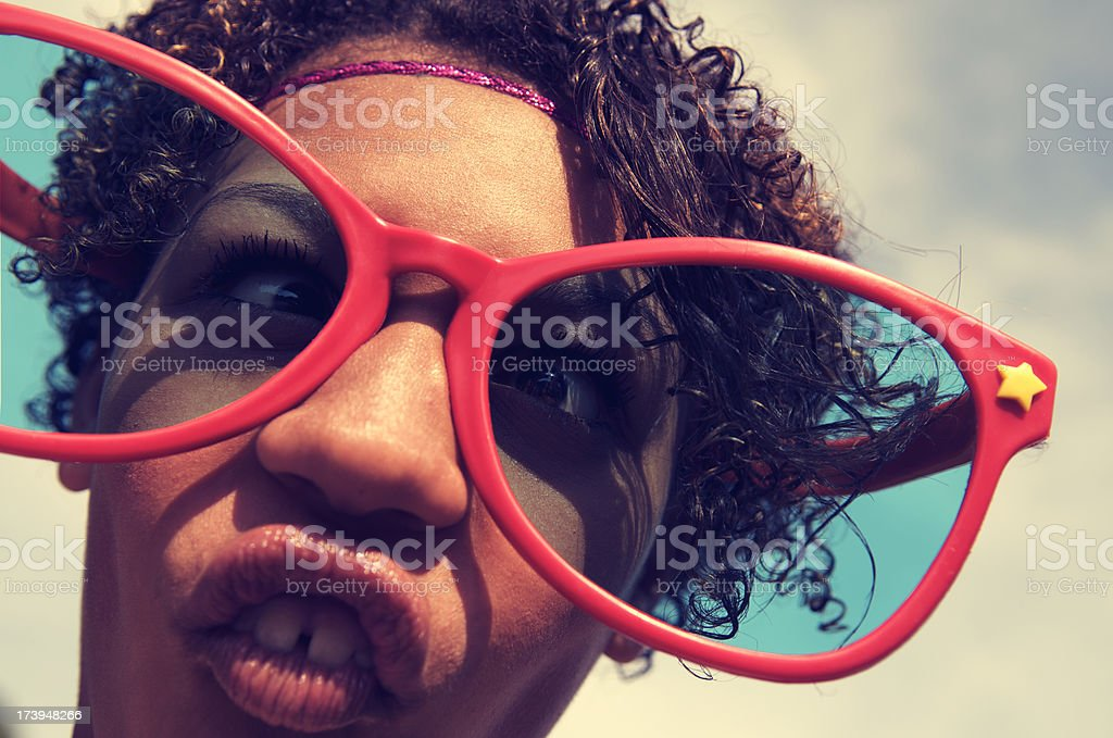 Girl Makes Goofy Face Behind Big Red Sunglasses royalty-free stock photo