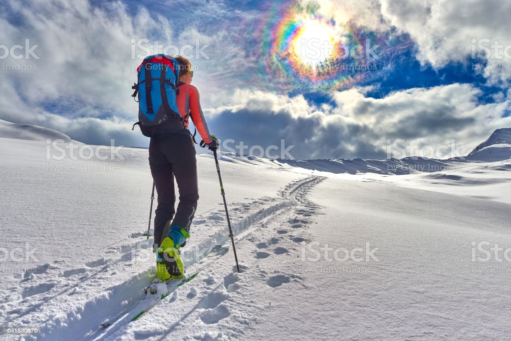 Girl makes ski mountaineering alone toward the mountain pass stock photo