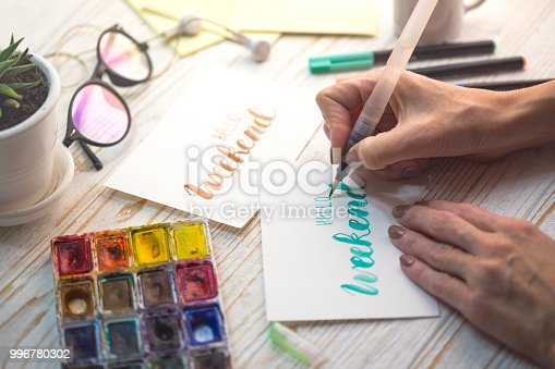 istock girl makes the inscription watercolor -  hello weekend 996780302