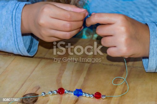colour image of a young girl making a bracelet out of colourful beads, hands only shot