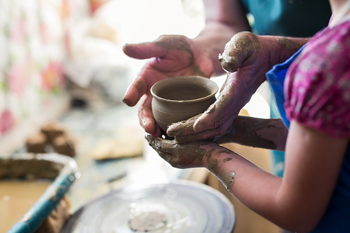 Girl making a clay bowl on sculpting wheel