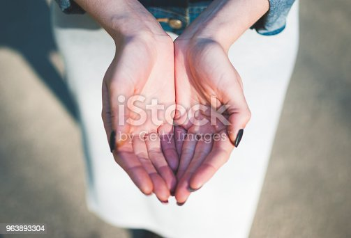 883034410 istock photo Girl making a cupped palms gesture against sunny asphalt background. 963893304