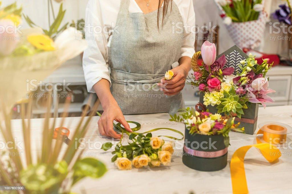 Female florist using scissors making beautiful bouquet at flower shop