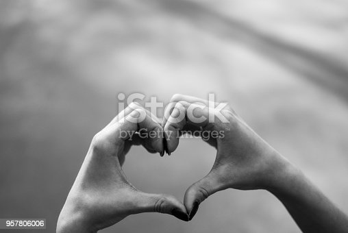 Girl making a heart shape gesture against grey asphalt background. Black and white