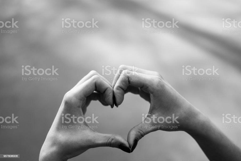 Fille faisant un coeur forme geste sur fond gris asphalte. - Photo