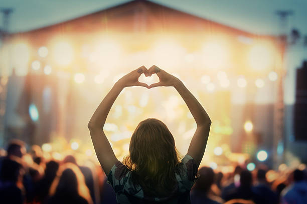 Girl making a heart-shape symbol for her favorite band. stock photo
