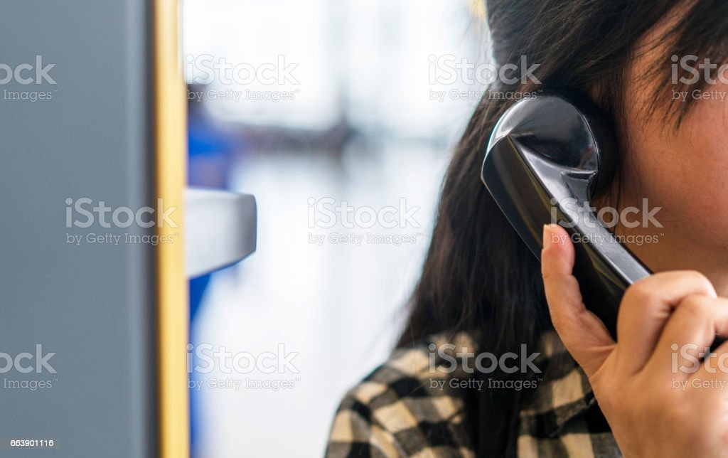 girl making a phone call in telephone booth stock photo