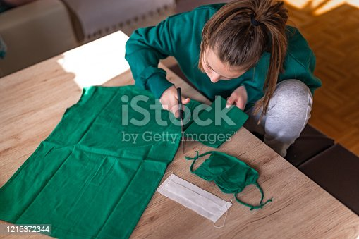 Young caucasian girl in a green sweater making a DIY protective face mask from a green cotton t-shirt at home during the coronavirus Covid-19.
