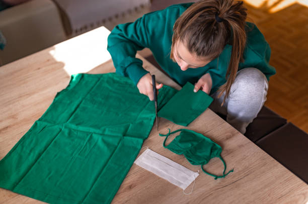 Girl making DIY protective face mask Young caucasian girl in a green sweater making a DIY protective face mask from a green cotton t-shirt at home during the coronavirus Covid-19. homemade stock pictures, royalty-free photos & images
