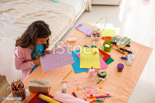High angle view of a girl cutting colored paper while making Easter decoration in her room.