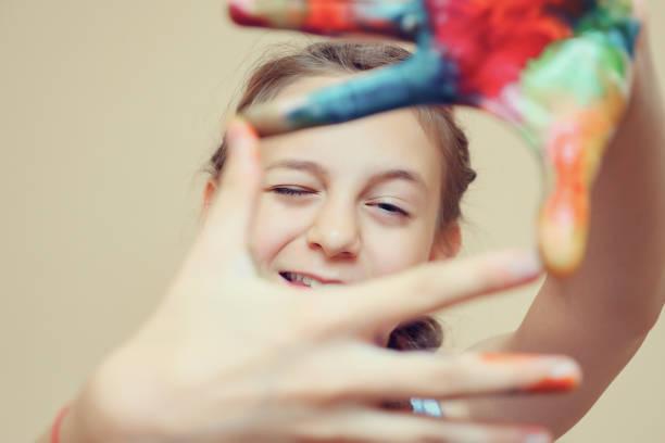 Mädchen macht Frame mit Händen in den Farben – Foto