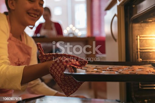 A girl is taking out gingerbread cookies of the oven.