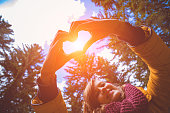 istock Girl making heart - shape symbol for love in the nature. 1043661584