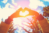 istock Girl making heart - shape symbol for love in the nature. 1043686408