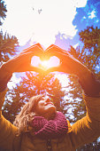 istock Girl making heart - shape symbol for love in the nature. 1044108566