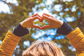 istock Girl making heart - shape symbol for love in the nature. 1051652308