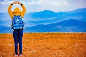 istock Girl making heart-shape symbol in hilly landscape. 1043673274