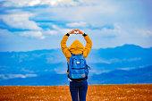istock Girl making heart-shape symbol in hilly landscape. 1044786398