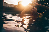 Girl in a swimming pool making a kissing face for the camera and holding up her hands in the shape of a heart at sunset with gentle sun flare