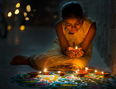 Girl making Rangoli and decorating with Oil lamps for Diwali