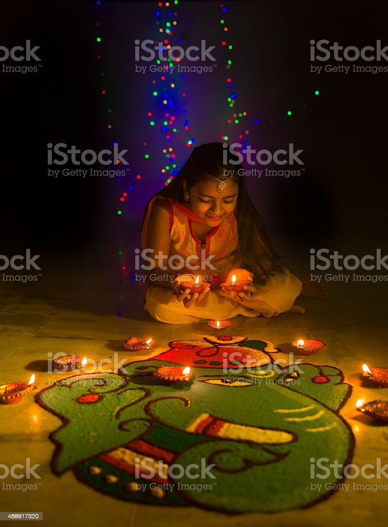 Girl making Rangoli and decorating with oil lamps for Diwali stock photo