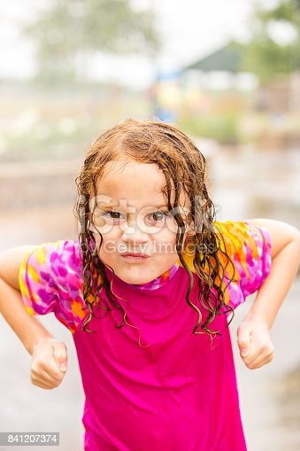 Close-up of a young girl making a silly face at the camera as she takes a break from playing in the fountains at an outdoors splash pad on an overcast summer day. She is pretending to be angry in this shot. The girl is wet from playing in the water. She has curly red hair and is wearing a pink rashguard swim shirt.