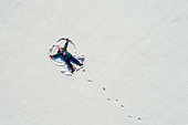 Little girl lying on the snow at sunny day and making snow angel. Photo taken with drone directly above