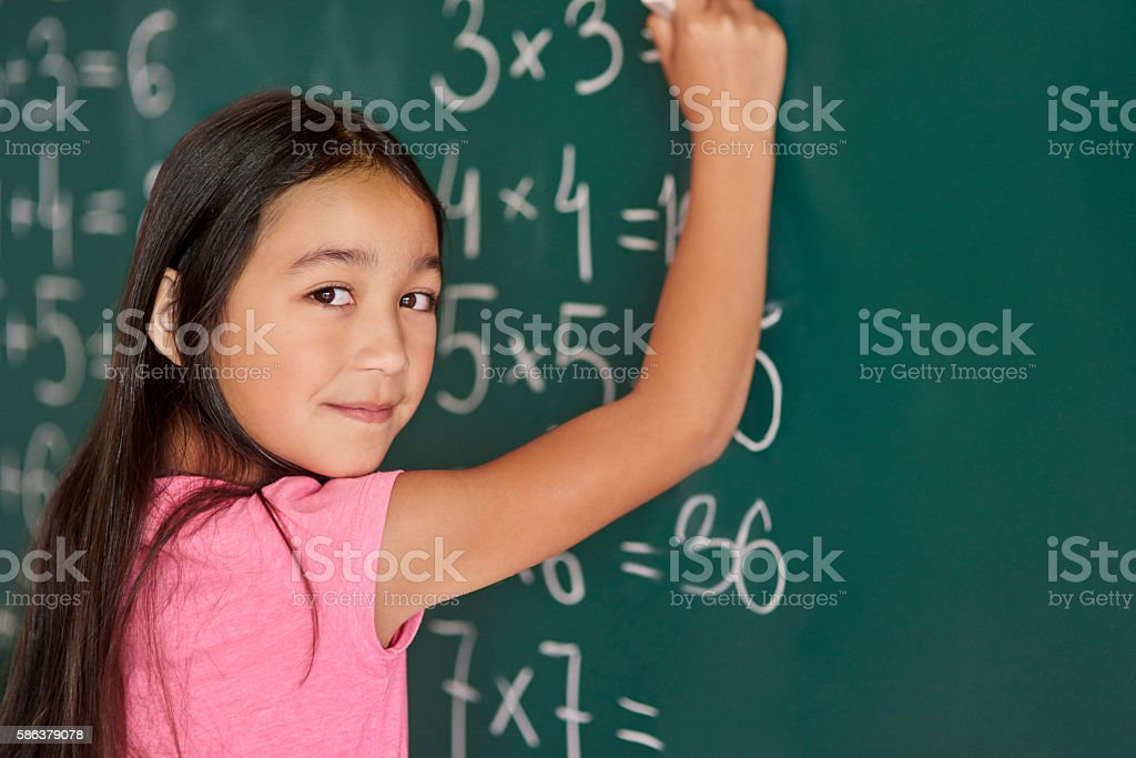 Girl making some exercises on the blackboard stock photo