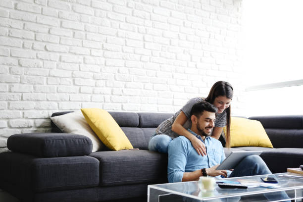 Girl Massaging Boyfriend On Sofa At Home stock photo