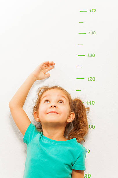 girl measure height with hand looking up - height measurement stock photos and pictures