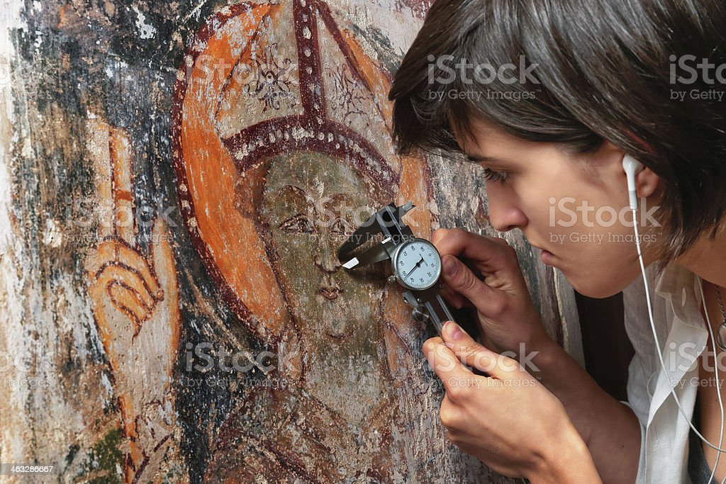 Girl measuring for renovation an ancient fresco. stock photo