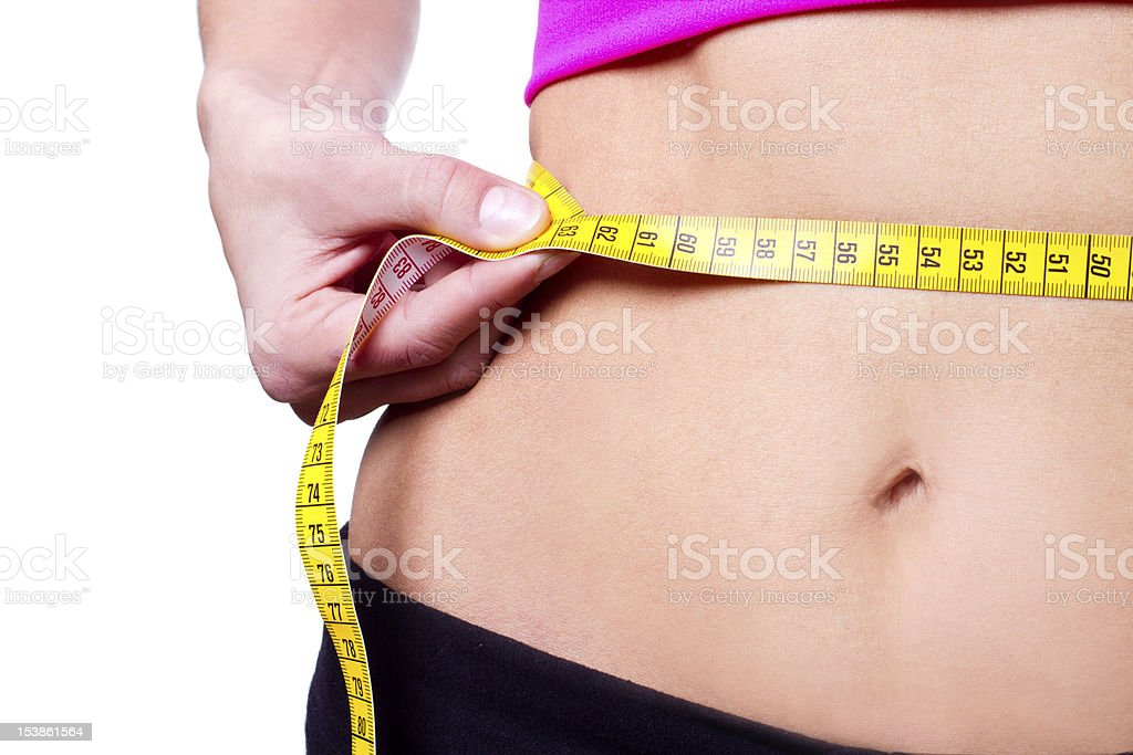 A girl measuring her waistline with a yellow measuring tape stock photo