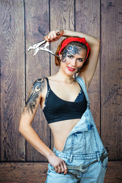 girl mechanic with face art posing with instruments. - jeans overall stock-fotos und bilder