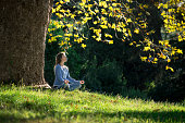 Girl meditates sitting on the grass under a maple tree in autumn