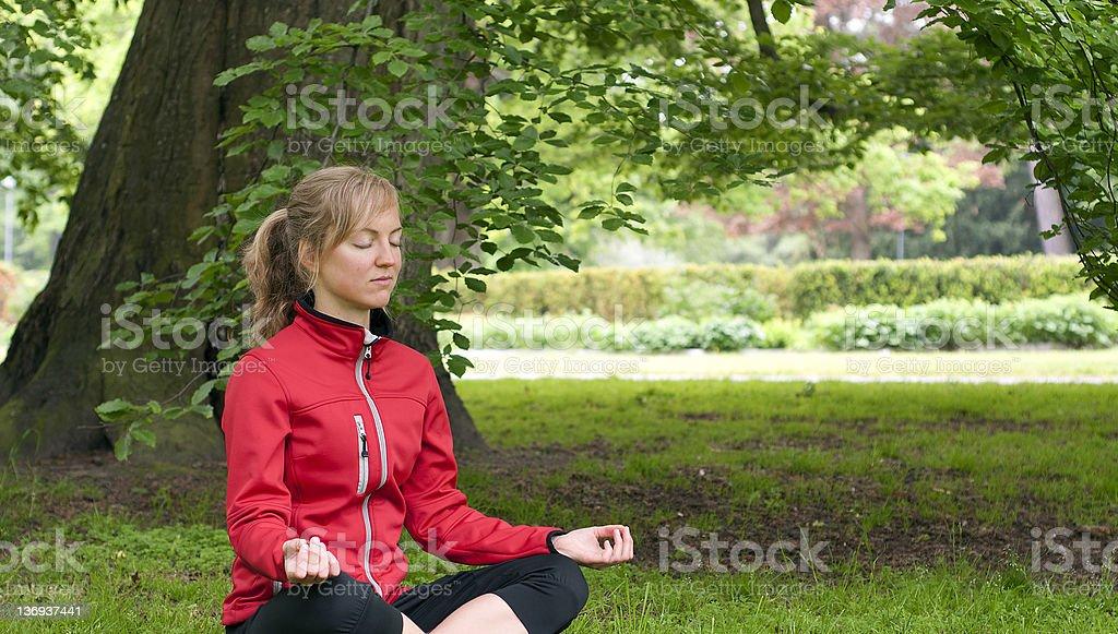 Girl meditates under a tree royalty-free stock photo