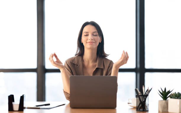 Girl meditating in office coping with stress Relaxation At Work. Calm businesswoman meditating at work, dealing with stress and anxiety. Free space well structure stock pictures, royalty-free photos & images