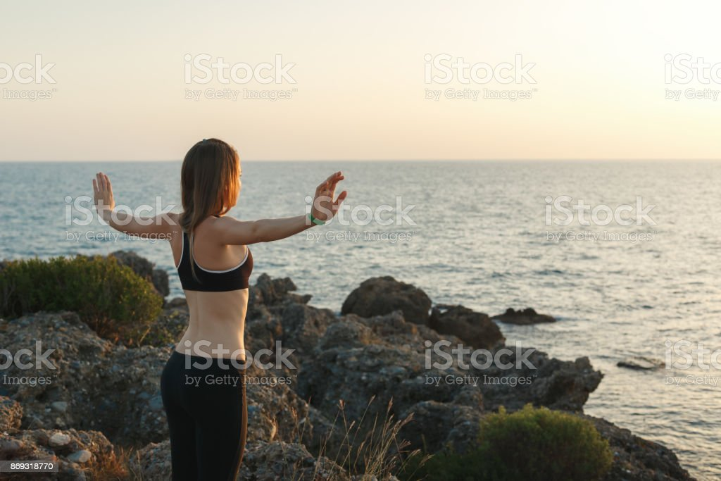 Girl meditating on the beach at sunset stock photo