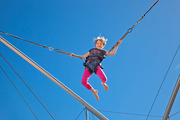 Girl Mid-Air in harness on Bungee Carnival Ride Amusement Park stock photo